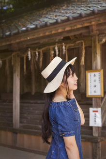 Young woman wearing blue dress and hat standing at Shinto Sakurai Shrine, Fukuoka, Japan. - MINF07734
