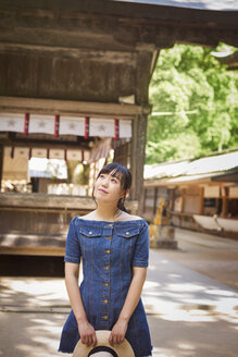 Young woman wearing blue dress and holding hat at Shinto Sakurai Shrine, Fukuoka, Japan. - MINF07737