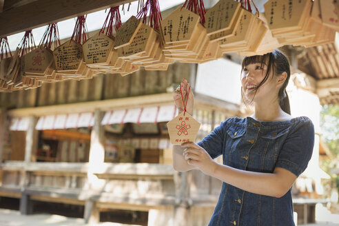 Young woman wearing blue dress looking at wooden fortune telling plaques at Shinto Sakurai Shrine, Fukuoka, Japan. - MINF07743