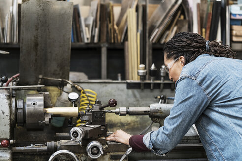 Woman wearing safety glasses standing in a metal workshop, working at a machine. - MINF07764