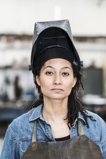 Portrait of woman wearing apron and welding mask standing in metal workshop, looking at camera. - MINF07767