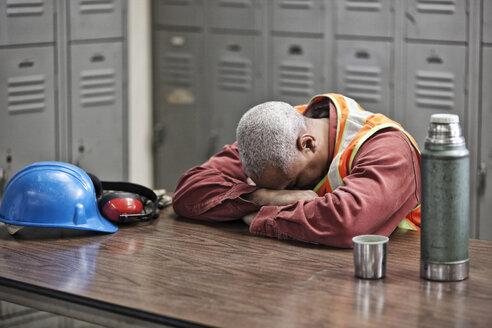 Black man factory worker taking a break from work in a factory locker room. - MINF07851