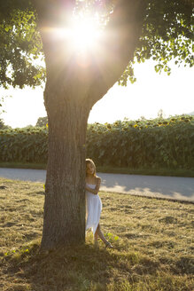 Girl leaning on tree trunk at summer evening - LVF07388