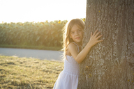 Girl leaning on tree trunk at summer evening - LVF07391