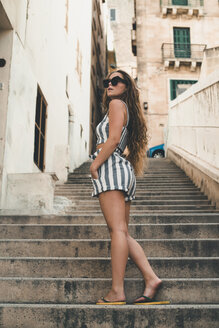 Teenage girl wearing striped beach wear, posing on stairs - ACPF00194
