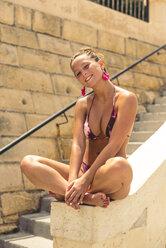 Teenage girl wearing bikini, sitting cross-legged on a wall - ACPF00206