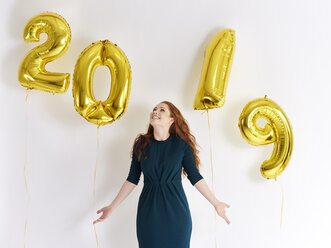 Happy young woman with golden balloons forming the date '2019' - ABIF00881