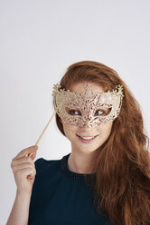 Portrait of smiling redheaded woman with masquerade mask - ABIF00884