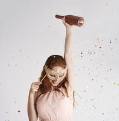Happy young woman with bottle of champagne and masquerade mask - ABIF00887