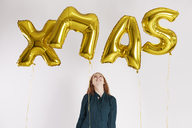 Young woman with golden balloons building the word 'xmas' - ABIF00893