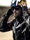 Bearded man wearing black leather jacket and sunglasses adjusting his yellow open face crash helmet. - MINF07949