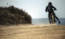 Rear view of man wearing crash helmet and black leathers riding cafe racer motorcycle on a dusty dirt road. - MINF07952