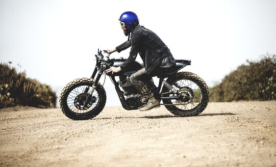 Side view of man wearing blue open face crash helmet and goggles riding cafe racer motorcycle on a dusty dirt road. - MINF07955
