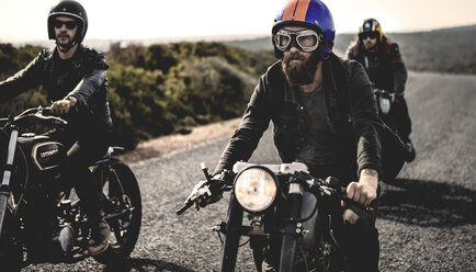 Three men wearing open face crash helmets and goggles riding cafe racer motorcycles along rural road. - MINF07958