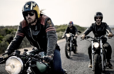 Three men wearing open face crash helmets and sunglasses riding cafe racer motorcycles along rural road. - MINF07961