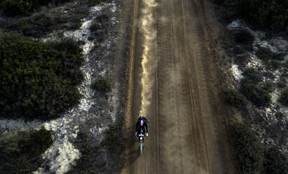 High angle view of man riding cafe racer motorcycle along dusty dirt road. - MINF07964