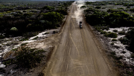Landscape with man riding cafe racer motorcycle along dusty dirt road. - MINF07967