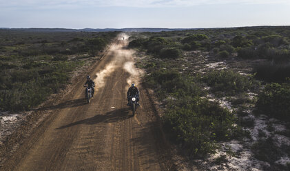 Landscape with two men riding cafe racer motorcycles in circles on a dusty dirt road. - MINF07970