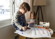 Boy with brown hair sitting indoors on a table, drawing with colouring pens, young girl beside him.. - MINF07985