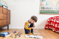 Boy with brown hair kneeling on hardwood floor in a nursery, playing with toy building bricks. - MINF07988