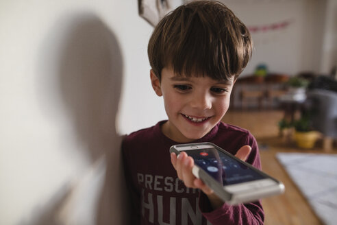 Smiling boy with brown hair standing indoors, holding smartphone. - MINF07997