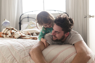 Man and smiling young girl lying on a bed. - MINF08012