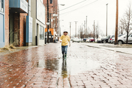 Boy wearing jeans and yellow hooded top walking through a puddle on red cobbled pavement. - MINF08015