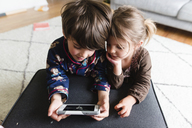 High angle view of boy and young girl lying indoors on their front, looking at smartphone. - MINF08021