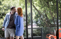 A couple standing on a balcony kissing. - MINF08069