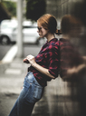 A woman leaning against a wall on a sidewalk. - MINF08093