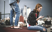 A woman sitting and using on a mobile phone on a city rooftop, with a man standing behind her. - MINF08099