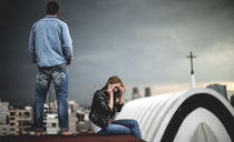 A woman sitting and talking on a mobile phone on a city rooftop, with a man standing behind her. - MINF08102