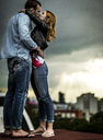 A couple standing and kissing on a city rooftop. - MINF08105