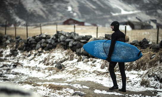 A surfer wearing a wetsuit and carrying a surfboard walking along a snowy beach. - MINF08108