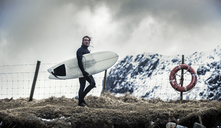 A surfer wearing wetsuits carrying a surfboard and walking past a life ring. - MINF08111