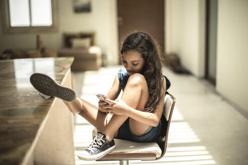A girl sitting looking at a mobile phone screen with feet up on a kitchen counter. - MINF08120