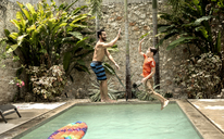A man and boy in mid air, jumping into a swimming pool. - MINF08129