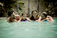 A family resting on a pool raft in a swimming pool, smiling into shot. - MINF08138