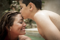 A boy kissing the forehead of a woman in a swimming pool. - MINF08141