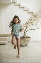A girl running in a house. - MINF08144