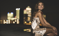 A young woman in a sequined party dress sitting on a rooftop at night. - MINF08180