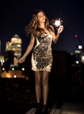 A young woman in a sequined dress dancing on a rooftop at night holding a party sparkler. - MINF08183