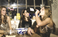 A group of friends around a table at a party, one girl drinking from a bottle of champagne. - MINF08186