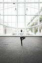 Businessman relaxing doing a yoga pose in a large open glass covered walkway. - MINF08205