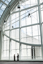 Businessman and woman meeting in a large glass covered walkway - MINF08211