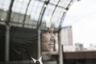 Caucasian businessman staring out a window with reflections. - MINF08214