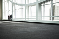 Businessman and woman meeting in a large glass covered walkway - MINF08220