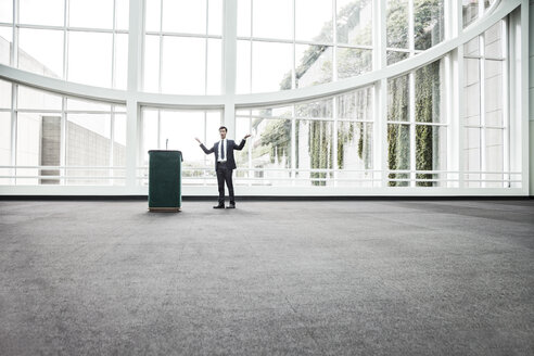 Businessman  at a podium with no one to talk to. - MINF08223