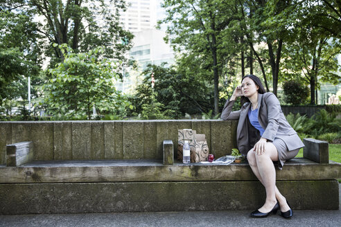 A businesswoman taking a break in a city park, seated on a bench with lunch. - MINF08226