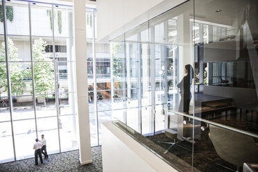 Businesswoman standing in a conference room window in a large business centre. - MINF08238
